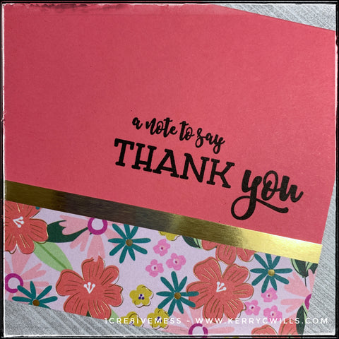 "A flat-lay view of the patterned detail on this handmade card. A floral pattern has shades of coral, pink, yellow and blue-green. Metallic gold accents add a splash of elegant detail beneath the sentiment, ""a note to say thank you"" which is stamped in black ink."