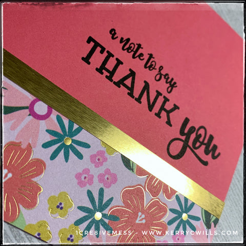 "An angled view of the floral patterned section on this handmade card front, the metallic gold accents are visible among the flowered pattern. A thin accent strip of metallic gold specialty paper divides the patterned paper from the stamped sentiment, ""a note to say thank you"" in black ink."