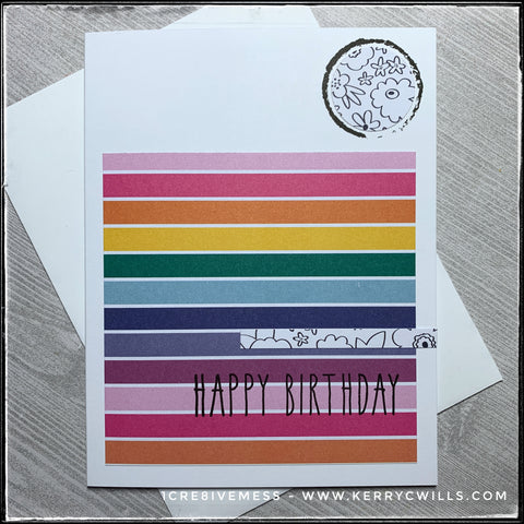 """A colorful handmade birthday card, ideal for helping them celebrate! A white card base lays the groundwork for a block of patterned paper which features a rainbow of horizontal stripes with thin white lines dividing between them. The words """"happy birthday"""" are stamped in black about 2/3 down the block in black ink. Near the top right corner is a circle of white paper with a black linear design of floral images. The same pattern continues on a thin strip extending from the right side above the sentiment. A wonky black circle has been stamped around the circular patterned piece. Layered beneath the card is a white envelope which is also included."""