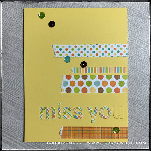 """A flat lay view of this handmade """"miss you"""" style card. Strips of patterned paper accent the die-cut letters that spell out """"miss you"""" and are accented by a smattering of sequins. The letter """"u"""" is the same color as the card base, to play off of the sentiment - missing you."""