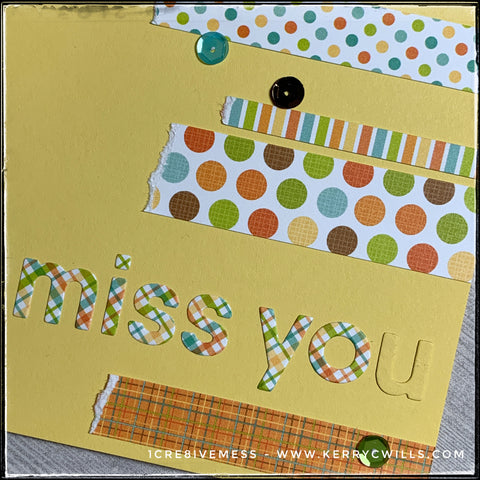 """An up-close, detailed view of the patterns and sequins on the front of this handmade card. Colorful strips of patterned paper have a purposely torn edge and surround the die-cut word """"miss you."""" Patterns include polka dots, stripes and plaids. A smattering of sequins spans across the card front as well for a slightly dimensional addition."""