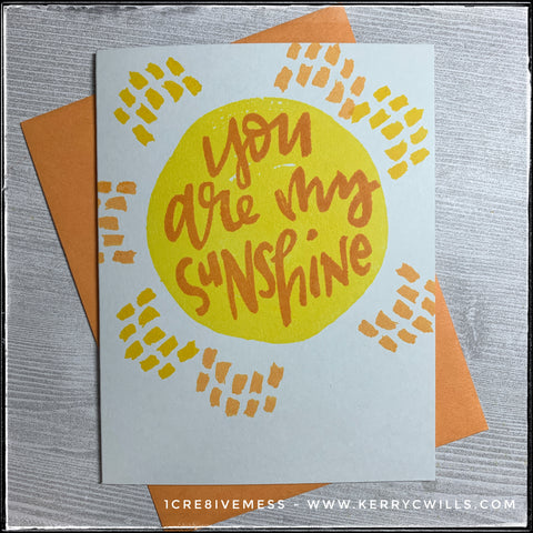 "A bright and happy card, this complimentary style card will make anyone's day better! A large watercolor inspired circle fills the card front in a bright shade of yellow. Surrounding the circle are small dashed lines that somewhat look like tiny rays in shades of darker yellow and light orange. Text fills the circle shape in a dark orange color and reads ""you are my sunshine"" in a fun and quirky font. The card base is a light grey and a light orange envelope is shown as well - it's also included with the card."
