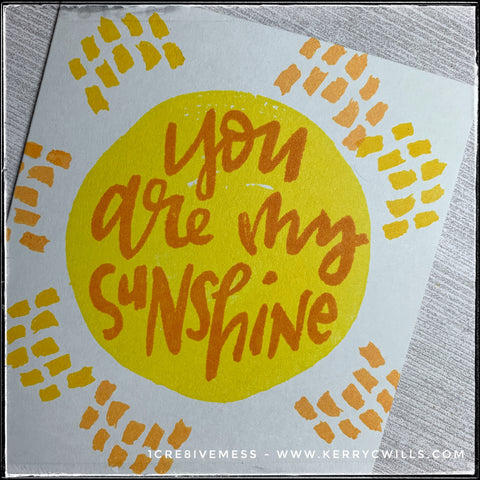 "An angled view of the details on this card front. You can see the layers of color that combine to create the sun-like image as well as the rays extending around it. The text that overlaps the circle image reads ""you are my sunshine"" in darker orange ink."