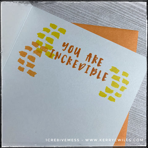 "The inside of this handmade card features the sentiment ""you are incredible"" stamped in dark orange ink and surrounded on both the left and right sides by more of those quirky dashed line groupings, twice in light yellow and once in light orange. There's plenty of room for a personal message beneath the stamped details."