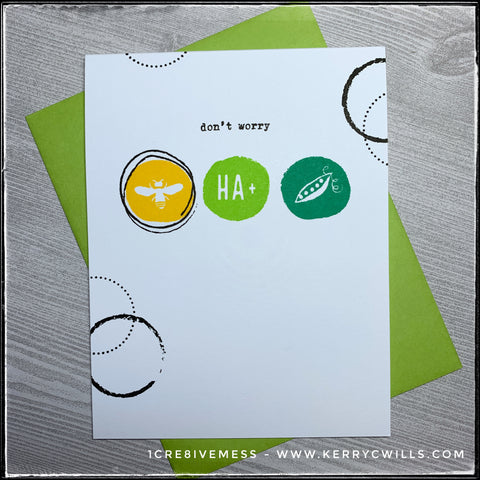 """This handmade card combines a word sentiment with images and clues to piece together the secondary sentiment. A white card base is accented on three sides by a variety of circles, stamped in black ink in two patterns; small tiny dots and what looks to be a paintbrush stroke. near the top middle of the card are the words """"don't worry"""" in a black typewriter font. Below that are three circles; yellow, lime green and then grass green from left to right. The yellow circle has the image of a bee, the lime green says HA+ and the grass green circle has the image of a pea. All together, the sentiment reads """"don't worry be happy."""" The colors are so vibrant and play well with the classic black and white design. A bright green envelope is shown and is included as well."""