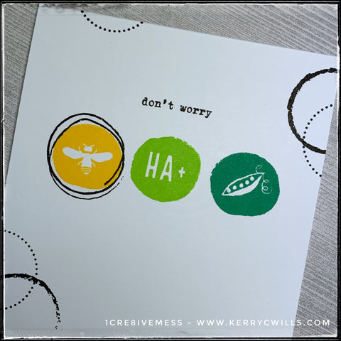 """An angled view of the front panel on this handmade card features three colorful circles in shades of yellow, lime green and grass green. On each of the circles is an image or a series of letters that combine to form a sentiment, along with the stamped words above them. When reading the entire card front, it reads """"don't worry be happy"""" The black and white classic design is timeless and this card is sure to make the recipient smile."""