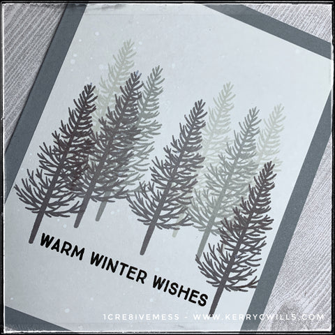 """An angled view of the details on this handmade card, specifically the cluster of winter trees in shades of greys and black. The sentiment """"warm winter wishes"""" is stamped in black ink near the bottom center of the card. White dots have been splattered across the card front to resemble freshly falling snow."""