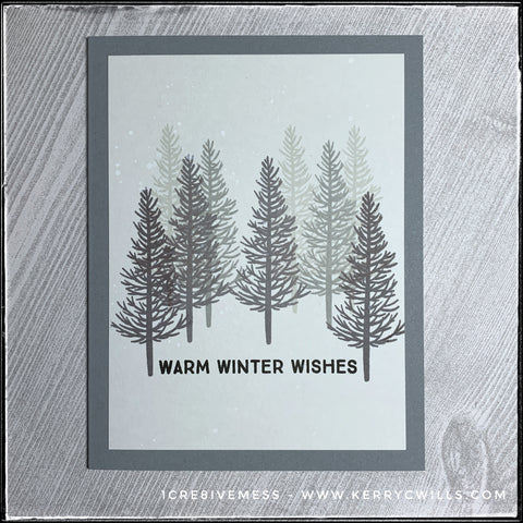 """A wintery scene fills the front of this handmade card. Trees that have lost their leaves are stamped in varying shades of grey creating a field of depth and dimension. The sentiment """"warm winter wishes"""" is stamped in black ink near the bottom middle of the card front."""
