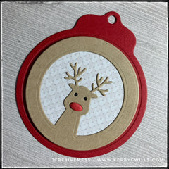 A red holiday tag with an inlaid design of a reindeer - most likely Rudolph. The inner background has the pattern of a sweater in shades of white and grey. The reindeer's nose is red and slightly dimensional as it's made from fun foam.