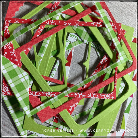 A pile of colorful scraps in shades of red and green in a variety of patterns all stacked haphazardly.