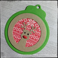 A green holiday tag with an inlaid design of a reindeer - most likely Rudolph. The inner background has the pattern of a sweater in shades of white and red. The reindeer's nose is red and slightly dimensional as it's made from fun foam.