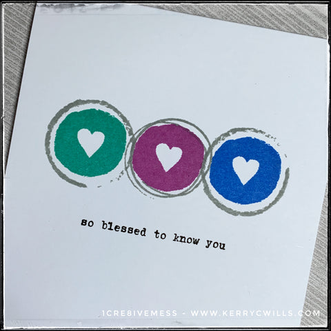 """An angled flat-lay of the details on this card front. Three colored circles in shades of aqua, deep purple and royal blue fill the card front. Each circle has the negative image of a heart in the center, allowing the white card base to show through. The stamped sentiment reads """"so blessed to know you"""" in black ink beneath the circles and hearts."""