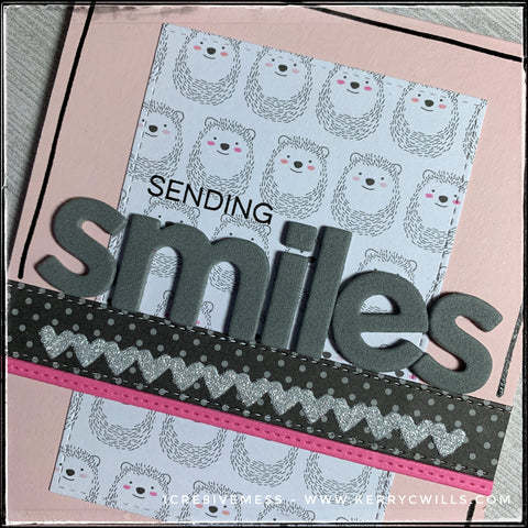 "An up close, detailed view of the background pattern full of smiling hedgehogs as well as the die-cut and stamped words combining to create the sentiment, ""sending smiles."""