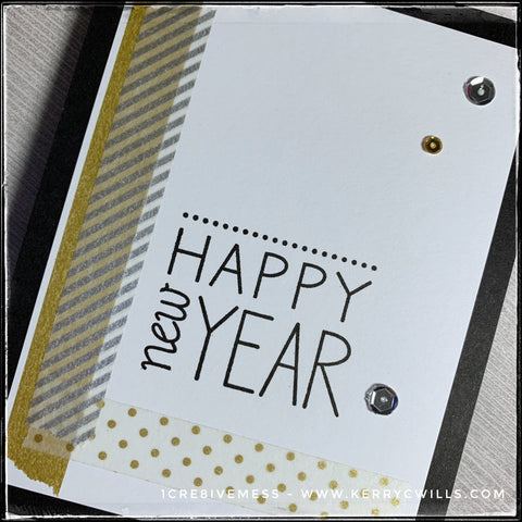"An angled, flat-lay view of this handmade card with decorative, multi-patterned washi tape strips alongside the sentiment ""Happy New Year."" A small scattering of gold and silver sequins add a splash of details."