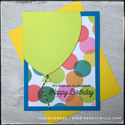 """This bright and colorful handmade card is ideal for celebrating a birthday! A large die-cut balloon fills the upper left corner of the card and even has a string made from black and white striped baker's twine. The background is full of colorful circles against a blue card base. Stamped on the polka dotted pattern is the sentiment which reads """"It's Your Day To Celebrate - Happy Birthday"""" in black ink. A bright yellow envelope is included."""