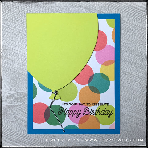 """The flat-lay view of this handmade card, designed with a celebratory birthday theme. A large die-cut balloon fills the card front against a colorful polka dotted patterned background which is accented with the stamped sentiment, """"It's your day to celebrate - Happy Birthday"""""""