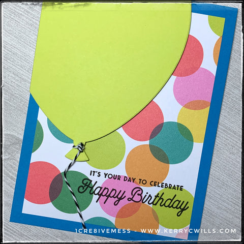 """An angled flat-lay of the card front where the sentiment is front and center. Stamped in black ink overlapping the colorful polka dotted background panel is the sentiment """"It's your day to celebrate - Happy Birthday."""" A die-cut balloon fills the upper left corner of the card base and is accented by black and white baker's twine."""