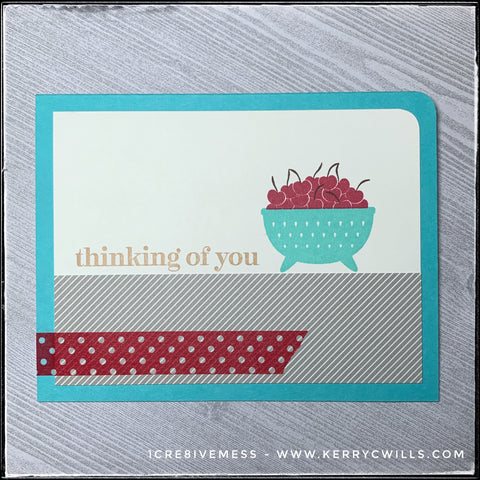 "The one rounded corner on this card in the upper right corner adds a soft detail to the otherwise slightly harsh corners and edges. The sentiment ""thinking of you"" is stamped directly above the horizontal panel of diagonally striped patterned paper and washi tape accent. The bowl of cherries adds a cheerful vibe."
