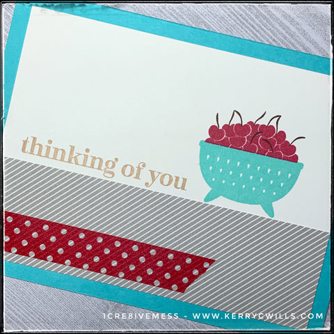 "An angled flat-lay of the card front where the sentiment and decorative elements are front and center. Stamped in kraft colored ink is the sentiment ""thinking of you."" A bowl of cherries sits to the right of the sentiment along the top edge of a decorative panel of striped cardstock."