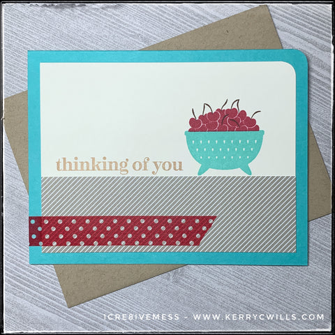 "This thinking of you style card combines several patterns via paper and washi tape along with a stamped image of a bowl of fruit. The sentiment ""thinking of you"" is stamped next to the bowl of cherries, above the block of tan and cream striped paper. Red and white polka dotted washi tape adds a little accent along the bottom portion of the card. The upper right corner of both the top panel and the turquoise card base have been rounded for additional detail. A kraft envelope is included and is show beneath the card."