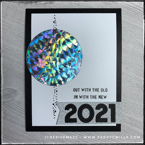 "A classic combination of black and white, this handmade new years themed card is accented by glitzy holographic cardstock and shimmer silver glitter. A large die-cut circle is half way down the card front near the left side, as if sliding down the vertical stretch of small black dots. The sentiment ""out with the old - in with the new"" is stamped in black ink above a glittery silver banner that holds the die-cut numbers ""2021"""