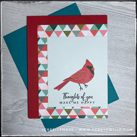 """Featuring a bright red cardinal, this handmade card will surely make the recipient smile! The sentiment """"Thoughts of you make me smile"""" is stamped in black in under the multi-layered stamped image of a cardinal which is layered on a multi-colored paper with a repeating triangular pattern. A red card base coordinates with the color of the bird and a deep teal envelope is shown and included."""