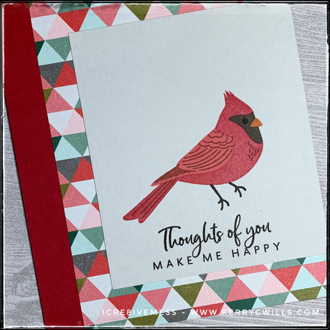 """An angled view of the stamped detail on this handmade card features a red cardinal and the sentiment, """"Thoughts of you make me smile."""" A triangular patterned paper adds a splash of color."""