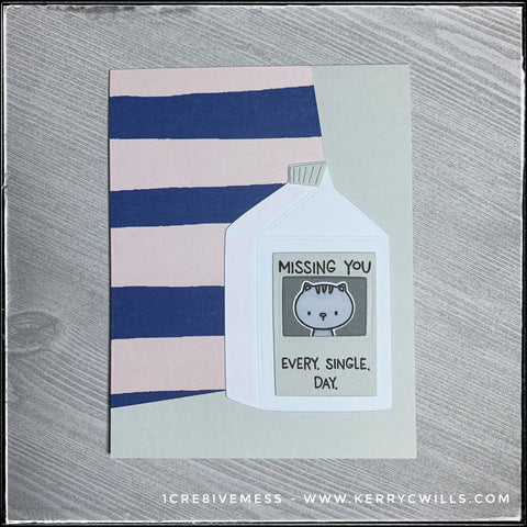 "A flat-lay view of this missing you style card. Stripes in a combo of pale pink and navy blue highlight the background behind a die-cut milk carton with the image of a tiny kitten and the stamped sentiment, ""Missing you. Every. Single. Day."""