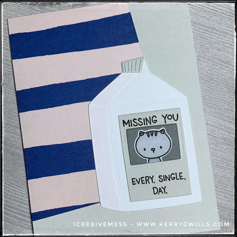 "An angled view of the detail on the die-cut milk carton, which features a die-cut, stamped and hand colored kitty cat. The sentiment ""Missing you. Every. Single. Day."" is stamped in black ink."