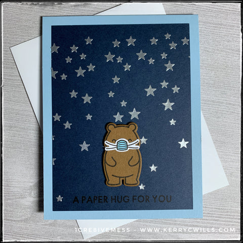 """Inspired by the attire required since the COVID outbreak, this card features a stamped and die-cut bear wearing a facemask. The background is dark blue and is filled with slightly dimensional stars, created from embossing paste and a stencil. Near the bottom of the card panel, the sentiment """"A paper hug for you"""" is stamped in black ink."""