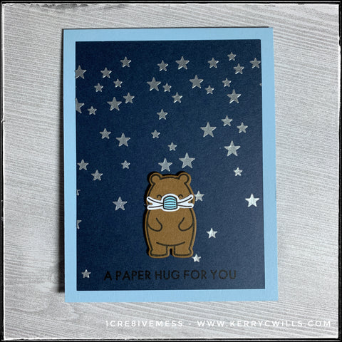 """""""A paper hug for you"""" is stamped in black ink near the bottom of the front of this card which features a background full of texture-embossed metallic silver stars and a dimensional stamped and die-cut bear wearing a face mask."""