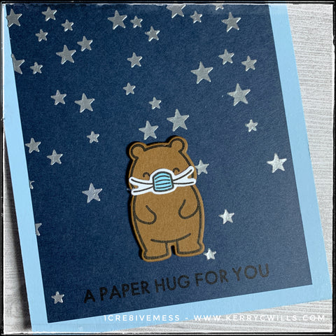 A diagonal view of the card front with emphasis on the die-cut bear wearing a safety mask along with a background created from a stencil and embossing paste.