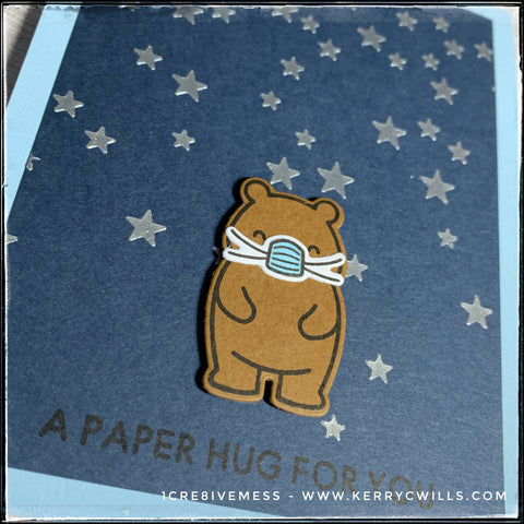 """An angled view of the card front, the dimension and shine of the starry background created with embossing paste is visible. The stamped and die-cut bear has been elevated off of the card base with foam tape. The sentiment """"A paper hug for you"""" is stamped in black ink near the bottom of the card front."""