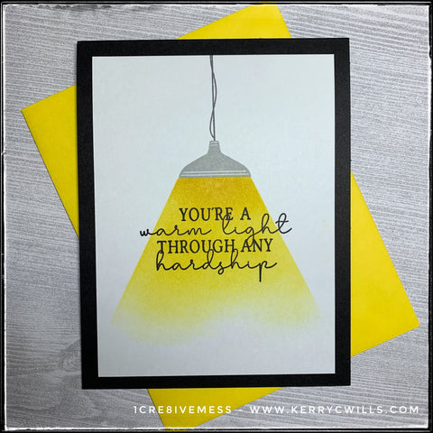 "An encouraging and uplifting handmade card, this front features a lamp with a glowing light around the sentiment ""You're a warm light through any hardship."" which is stamped in black ink. A bright yellow envelope is shown with the card and is included."