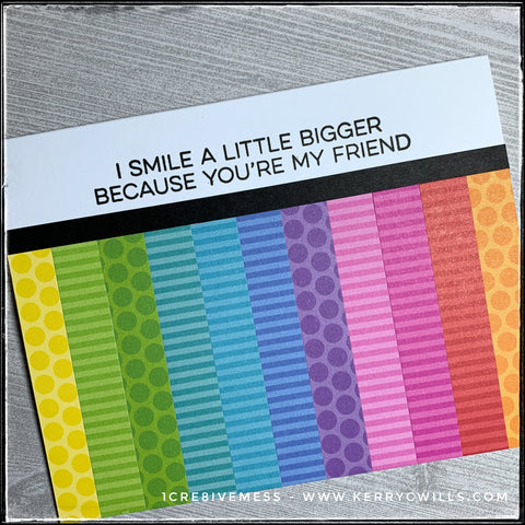 """An angled view of the card front - all the colors are visible in their vertical stripes and polka dotted or striped patterns. The sentiment is stamped in black ink which is very bold along the white open space. It reads """"I smile a little bigger because you're my friend."""" and is sure to make the recipient smile. What a great way to share some happiness."""
