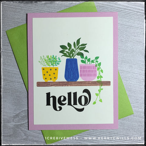 """This handmade card has a wonderful scene full of potted plants, along the stamped sentiment, """"hello."""" The plants feature a variety of shades of green in colorful pots with stripes and polka dots. The card base is a lovely shade of pinkish-lavender and a green envelope is included."""