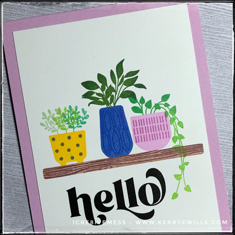 """An angled, detailed view of the plants on the front of this handmade card. Three pots, yellow with polka dots, blue with a linear pattern and light purple with dashes all hold clusters of green leaves. The pots are made to look as though they are sitting on a wooden shelf. The sentiment """"hello"""" is stamped near the bottom of the card front in a big, bold black font."""