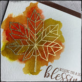 "Up close details of a handmade card from 1cre8ivemess with a watercolored background behind a heat embossed geometric gold leaf. Stamped with the sentiment ""Wishing you a season of blessings"" in brown ink."