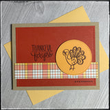 "A pale yellow envelope accompanies this fall themed card, perfect for the season of thanksgiving. A red-orange panel has been die-cut and features faux stitch marks along the perimeter of the rectangle. A narrow horizontal strip with a plaid pattern in shades of yellow, orange, brown and white sits near the bottom of the card front. A light orange circle is elevated off of the card base and is stamped with a brown turkey near the sentiment ""thankful for you""."