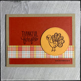 "A flat-lay view of this fall themed card, perfect for the season of thanksgiving. A red-orange panel has been die-cut and features faux stitch marks along the perimeter of the rectangle. A narrow horizontal strip with a plaid pattern in shades of yellow, orange, brown and white sits near the bottom of the card front. A light orange circle is elevated off of the card base and is stamped with a brown turkey near the sentiment ""thankful for you""."