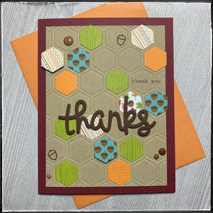 "a fall-inspired thank you card, this front panel features an de-bossed hexagonal pattern on which several patterned hexagons are overlapped. there's a large die-cut word ""thanks"" that combines cardstock as well as fun foam for a dimensional sentiment. a smattering of small epoxy dots add additional detail across the card front."