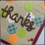 "diagonal up close photo of the details on this card front, including the patterns on the cardstock as well as the layers of the word ""thanks"" and the enamel dots. the patterns include colorful leaves, rustic acorns and a woodgrain pattern."