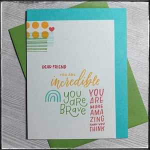 "Grounded on an aqua card base, a light grey panel is lined up with the left and bottom sides of the base so a border is shown on the top and right hand side. A cluster of text fills the center of the grey panel in a variety of colors, including aqua, green, yellow-orange, pink and red. Sentiments include: ""dear friend"", ""you are incredible"", ""you are brave"", and ""you are more amazing than you think"". Near the top of the panel on the left hand side are several patterns including dashed lines, small circles a"