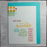 A flat-lay view of this handmade card full of encouraging and uplifting sentiments in a variety of colors and fonts. Dashed lines and dots along with a small heart accent the top left corner of the grey card panel that's mounted on an aqua card base. Four positive sentiments are stamped in a rainbow of colors.