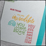 "An up-close photo showing the detail of the stamped sentiments. ""Dear Friend"" is stamped in red, ""You are incredible"" in yellow-orange, ""you are brave"" is in green and ""You are more amazing than you think"" is in pink. A small three-ray rainbow is stamped in aqua and matches the card base."