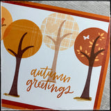 "An up close detailed view of several of the stamped trees and the details on the tree tops. Thin striped lines are crisp and clear in a medium shade of orange. The lightest colored tree top is a beautiful plaid pattern with an inlaid heart design. The third tree top shown is the darkest color orange and features some lighter orange colored leaves. The sentiment ""autumn greetings"" overlaps the trunk of the middle tree in two shades of orange ink which are blended in an ombre color scheme."