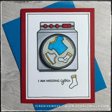 "A handmade card designed to send to a friend or family member who you've been missing! Front and center is a stamped and die-cut washing machine that's been hand colored. The center portion of the washing machine that resembles the drum is elevated off of the card base with a small plastic spring so that it moves back and forth when flicked. The sentiment ""I am missing you"" is accented by a lonely sad sock. The red card base coordinates nicely with the bright blue envelope that's included."
