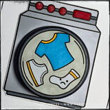 An angled up close view of the drum of the washing machine on this handmade card. A tiny pair of underroos along with a t-shirt and sock are floating in the washing machine. Propelled by a small plastic spring that lays flat when mailing the card, the circle die-cut wiggles back and forth as a fun detail.