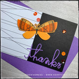 "An up close, detailed flat-lay view of the embellished corner of this slimline card. The die-cut butterfly has been stamped in two shades of orange and the intricate details have been stamped in black ink. Cardstock is layered over fun foam for added dimension. The word ""thanks"" has been die-cut from purple cardstock and sits near the lower right corner. A smattering of sequins adds detail and the perfect amount of glitz and shine."