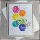 "A bright and colorful handmade card with an embossed hexagonal texture! The front of this card has six hexagons that are stamped in a watercolor method in rainbow order. The sentiment ""oh, hello there"" is stamped in black ink, slightly overlapping the colored hexagons. The panel has been elevated off of the card base for added dimension and three small clear dots accent the design. Hand drawn black lines outline the perimeter of the light grey card base. A white envelope is layered under the card and is als"